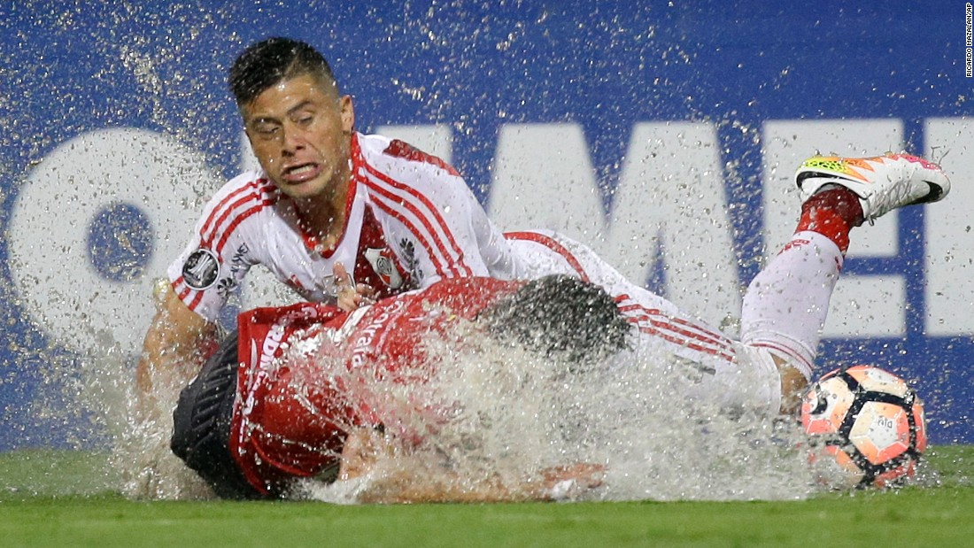 Soccer players splash into the turf Wednesday, March 15, during a rainy Copa Libertadores match in Medellin, Colombia. Argentine club River Plate defeated Independiente 3-1.