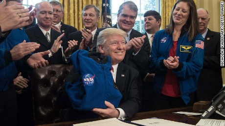 President Donald Trump displays a NASA jacket after he signed a bill increasing funding for NASA in the Oval Office at the White House in Washington, DC, on March 21, 2017.