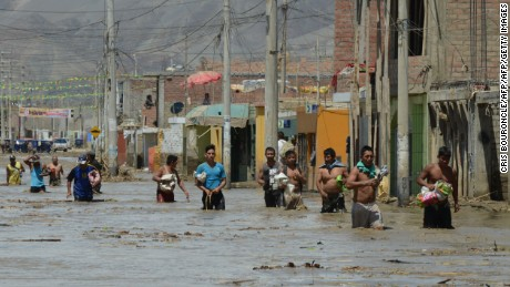 Local residents of the town of Huarmey, 300 kilometres north of Lima, wade through muddy water in the street on March 19, 2017 after a flash flood hit the evening before. The El Nino climate phenomenon is causing muddy rivers to overflow along the entire Peruvian coast, isolating communities and neighbourhoods. Thousands have been affected since January, and 72 people have died. Most cities face water shortages as water lines have been compromised by mud and debris. / AFP PHOTO / CRIS BOURONCLE        (Photo credit should read CRIS BOURONCLE/AFP/Getty Images)