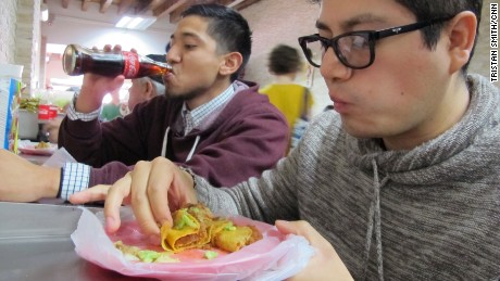 Matadamas, left, and his cousin, Daniel Velasco,  eating at a taco stand.