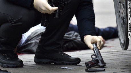 A Ukrainian police officer seizes a gun at the scene where Voronenkov was shot dead on Thursday.