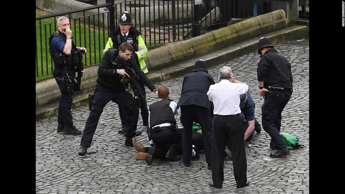 "An armed police officer stands over the attacker, identified as Khalid Masood, on the ground outside the Palace of Westminster in London on Wednesday, March 22. <a href=""http://www.cnn.com/2017/03/23/europe/khalid-masood-london-attacker-what-we-know/index.html"" target=""_blank"">Police identified Masood</a>, a 52-year-old England native with a long criminal record, as the man whose <a href=""http://www.cnn.com/2017/03/23/europe/london-attack/index.html"" target=""_blank"">attack in London</a> left <a href=""http://www.cnn.com/2017/03/23/europe/london-parliament-terror-attack-victims/index.html"" target=""_blank"">at least four people dead</a> and 40 injured. ""It appeared that a car was coming towards the House of Commons mowing down pedestrians on the way,"" said Member of Parliament Gerald Howarth. ""The driver then got access to the parliamentary estate, stabbed a police officer and was shot."" See related story: <a href=""http://www.cnn.com/2017/03/22/world/tobias-ellwood-london-rescue/index.html"" target=""_blank"">Amid London chaos, MP rushes to victim's aid</a>"