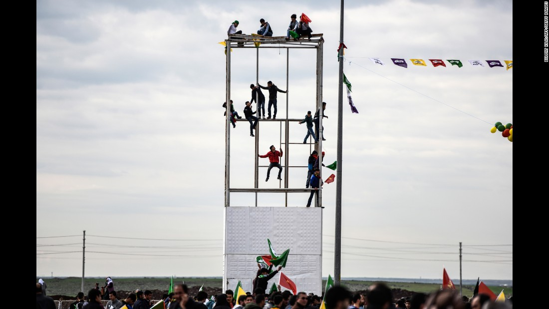 "Young men in Diyarbakir, southeastern Turkey, climb and sit on a scaffolding as Turkish Kurds gather for Nowruz celebrations on Tuesday, March 21. <a href=""http://www.cnn.com/videos/world/2017/03/20/persian-new-year-what-you-need-to-know-haft-seen-nowruz-ctw-orig.cnn/video/playlists/mobile-digital-shorts/"" target=""_blank"">Persian New Year</a>, or Nowruz, is an ancient celebration marking the first day of spring and is celebrated by millions around the world."