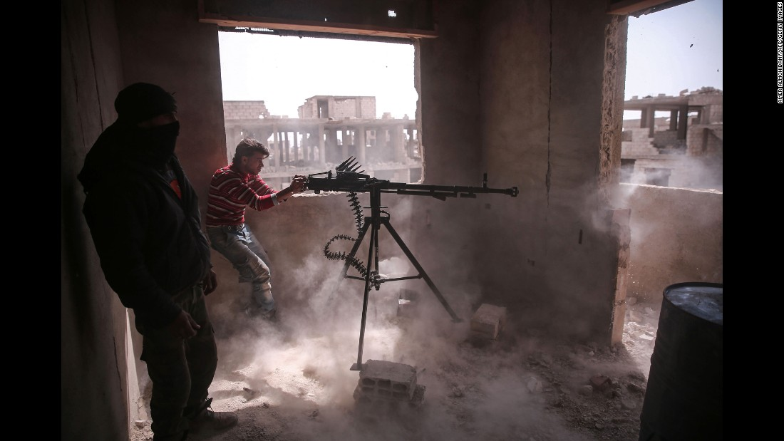 "An opposition fighter from the Faylaq al-Rahman brigade fires a machine gun in Jobar, a rebel-held district in the Syrian capital of Damascus, on Sunday, March 19. The clashes broke out <a href=""http://www.cnn.com/2017/03/19/middleeast/damascus-surprise-attack-syria/"" target=""_blank"">after a surprise rebel attack</a>."