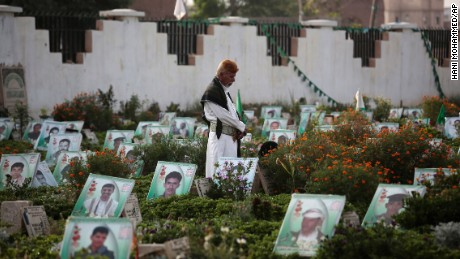 A Yemeni man offers prayers at the portrait adorned grave of his relative who was killed in the ongoing conflict in Yemen, at cemetery in Sanaa.