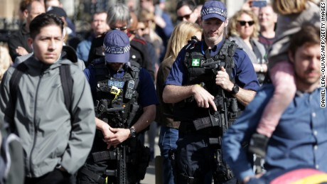 Armed British police officers carry their weapons as they patrol during Saturday's march.