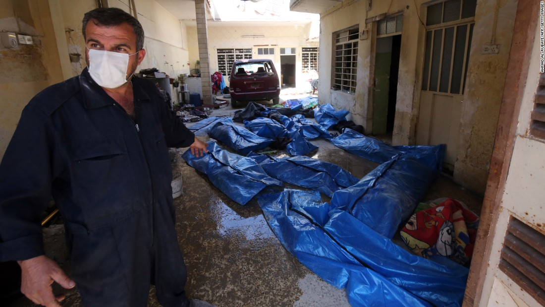 An Iraqi rescue worker gestures towards bodies wrapped in plastic in the al Jadidah area on March 26, 2017, following airstrikes in which civilians were reportedly killed.