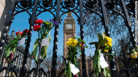 TOPSHOT - Floral tributes to the victims of the March 22 terror attack are seen on outside the Houses of Parliament in Westminster, central London on March 27, 2017. British police investigating a deadly attack on parliament made a new arrest Sunday as officials set their sights on accessing WhatsApp, the heavily-encrypted messaging service that was used by the killer. / AFP PHOTO / Justin TALLIS        (Photo credit should read JUSTIN TALLIS/AFP/Getty Images)