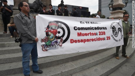 Two journalists hold a banner displaying the number of journalists dead (228) and disappeared (29) in the past 33 years in Mexico, during a protest against the recent murder of the correspondent journalist Miroslava Breach, of La Jornada newspaper, at the Angel de la Indepencia in Mexico City, on March 25, 2017.  Breach, who investigated drug gangs, was found murdered earlier this week in Chihuahua, northern Mexico near the US border, with multiple gunshot wounds to the head. / AFP PHOTO / ALFREDO ESTRELLA        (Photo credit should read ALFREDO ESTRELLA/AFP/Getty Images)