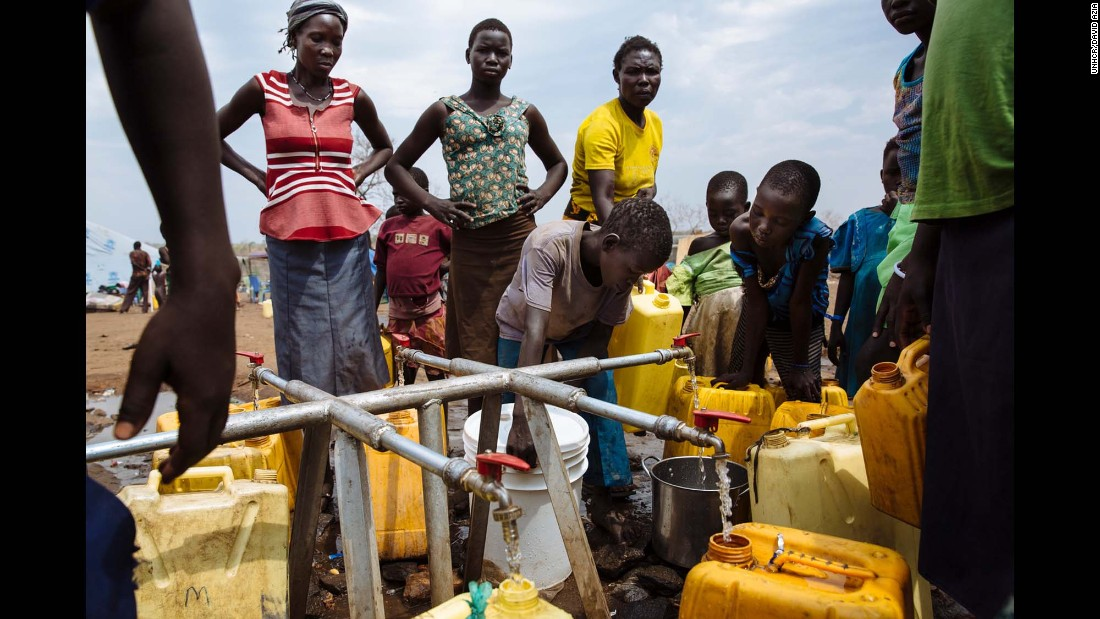 South Sudanese refugees fill jerrycans and other containers with water at the Imvepi Reception Centre, Arua District, Northern Region, Uganda.