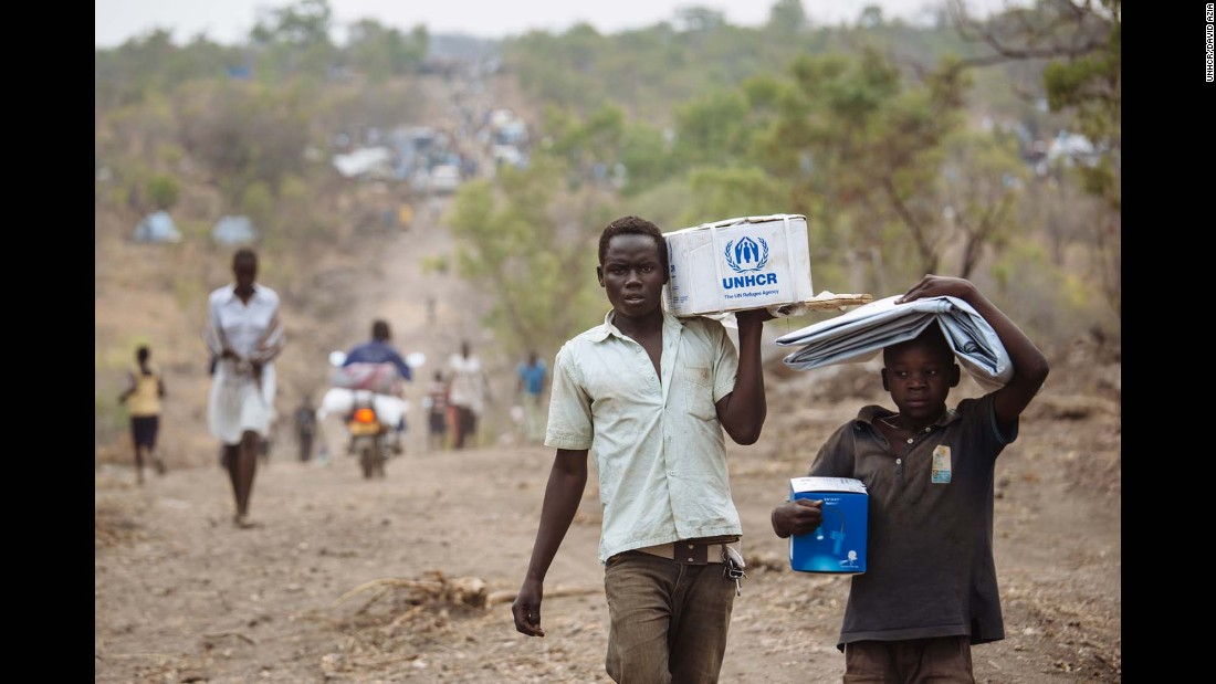South Sudanese refugees carrying Core Relief Items walk down a road in Bidibidi refugee settlement, Yumbe District, Northern Region, Uganda.