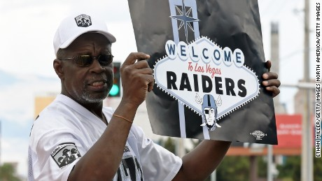 LAS VEGAS, NV - MARCH 27:  Oakland Raiders fan Davi Tole of Nevada displays a sign to passing motorists on the Las Vegas Strip near the Welcome to Fabulous Las Vegas sign after National Football League owners voted 31-1 to approve the team's application to relocate to Las Vegas during their annual meeting on March 27, 2017 in Las Vegas, Nevada. The Raiders are expected to begin play no later than 2020 in a planned 65,000-seat domed stadium to be built in Las Vegas at a cost of about USD 1.9 billion.  (Photo by Ethan Miller/Getty Images)