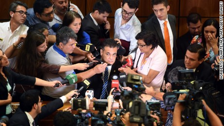 Paraguay's senate president Roberto Acevedo (C) is hounded by journalists during a press conference in Asuncion, on March 28, 2017. Supporters of President Horacio Cartes unexpectedly formed a parallel senate to aprove a constitutional amendment authorizing his reelection, opposing senator Robeto Acevedo said.   / AFP PHOTO / NORBERTO DUARTE        (Photo credit should read NORBERTO DUARTE/AFP/Getty Images)