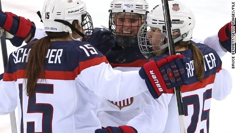 Members of the US women's hockey team celebrate after scoring a goal at the 2014 Winter Olympics.