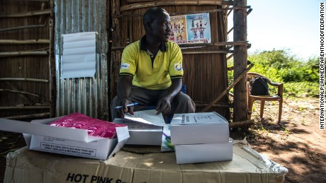 A member of staff from IPPF-affiliated Reproductive Health Uganda distributes free condoms during a mobile clinic visit to the village of Ochaga, near Gulu, Uganda.