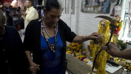 Doña Queta Romero touches a Santa Muerte statue outside her home.