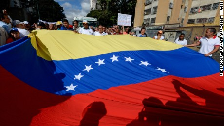 Health care workers holding a Venezuela's national flag demonstrate against President Nicolas Maduro's government, the lack of medicines and low salaries in the country, in Caracas on February 7, 2017. / AFP / FEDERICO PARRA        (Photo credit should read FEDERICO PARRA/AFP/Getty Images)