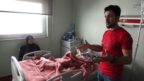 Ala'a Al-Tai describes how he and his mother, Aliya (sitting on the left), pleaded with ISIS fighters to let them leave and find treatment for his wounded daughter, who is now recovering at West Erbil emergency hospital.