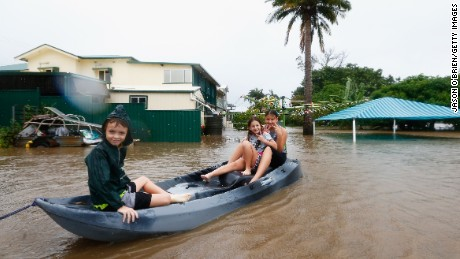 Three children paddle in a kayak  after flood waters entered their backyard on March 30, in Murwillumbah, Australia.