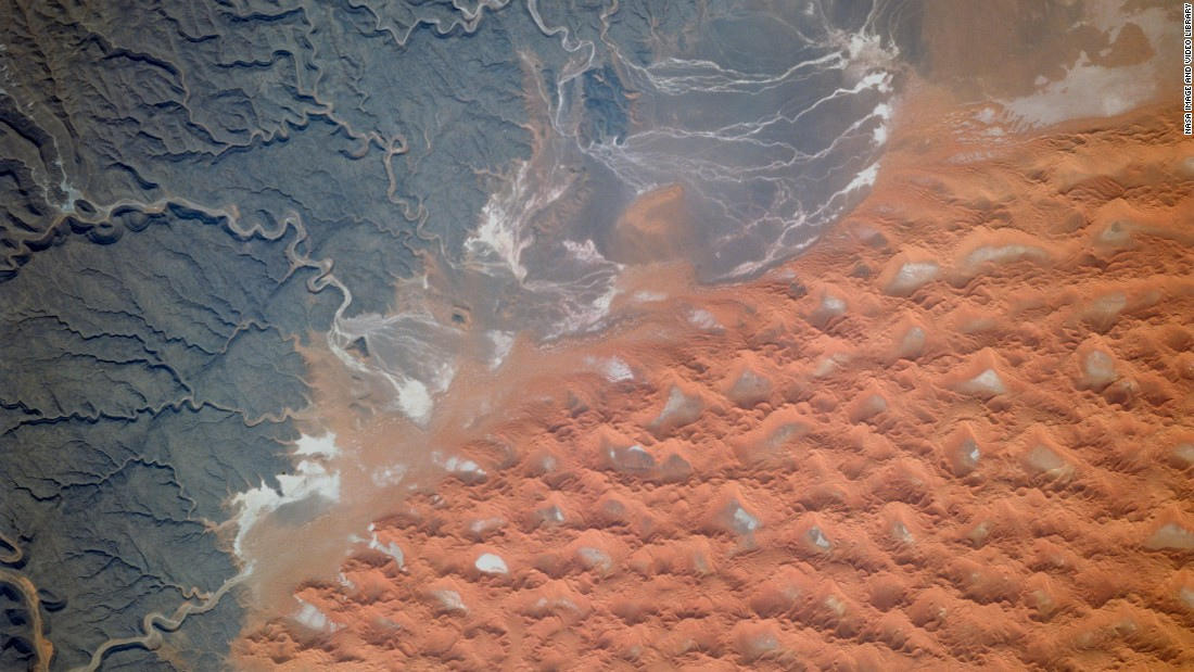 "The Tifernine dunes of east-central Algeria are pictured in this image, captured in 1995. ""The dunes lie in a basin of dark-colored rocks heavily cut by winding stream courses (top right),"" explains the caption in the Nasa Image and Video Gallery. ""Very occasional storms allow the streams to erode the dark rocks and transport the sediment to the basin. Winds then mold the stream sediments into the complex dune shapes so well displayed here."""