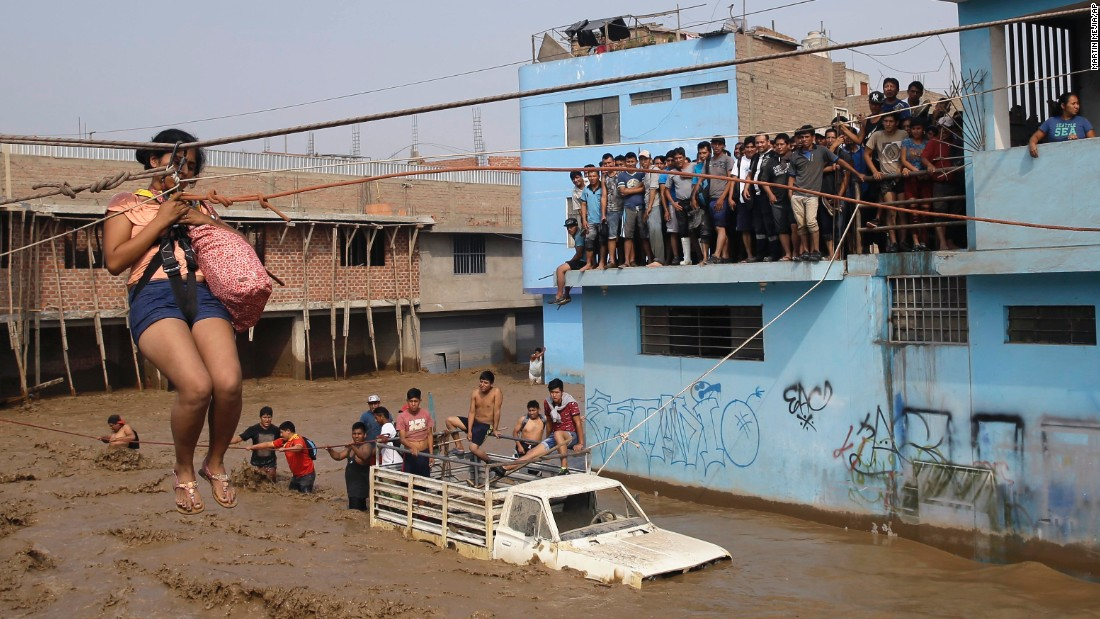 "A woman in Lima, Peru, is pulled to safety on Friday, March 17. More than half a million people in and around Lima <a href=""http://www.cnn.com/2017/03/20/americas/peru-floods-mudslide-toll/"" target=""_blank"">have been affected by storms and flooding,</a> authorities said. Weeks of rain have caused rivers across the country to rise."