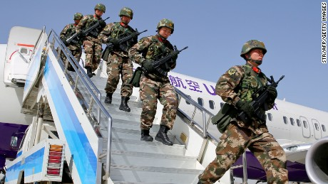 Chinese military police get off a plane to attend an anti-terrorist oath-taking rally in Xinjiang, on February 27.