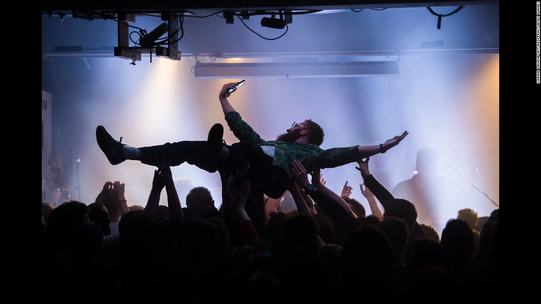 A crowd surfer snaps a selfie Tuesday, March 21, during a Frank Carter & The Rattlesnakes concert in Belfast, Northern Ireland.