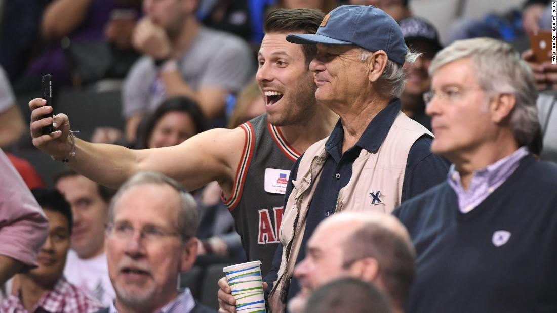 An Arizona basketball fan takes a selfie with actor Bill Murray during an NCAA Tournament game on Thursday, March 23. Murray's son Luke is an assistant coach for Xavier University, which defeated Arizona in the Sweet 16.