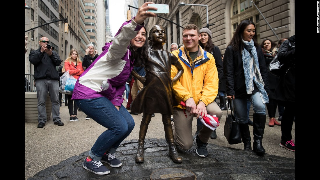 "Visitors pose for a selfie next to the <a href=""http://www.cnn.com/2017/03/09/us/gallery/fearless-girl-wall-street/index.html"" target=""_blank"">""Fearless Girl"" statue</a> in New York City on Monday, March 27. The statue faces Wall Street's iconic sculpture of a charging bull."