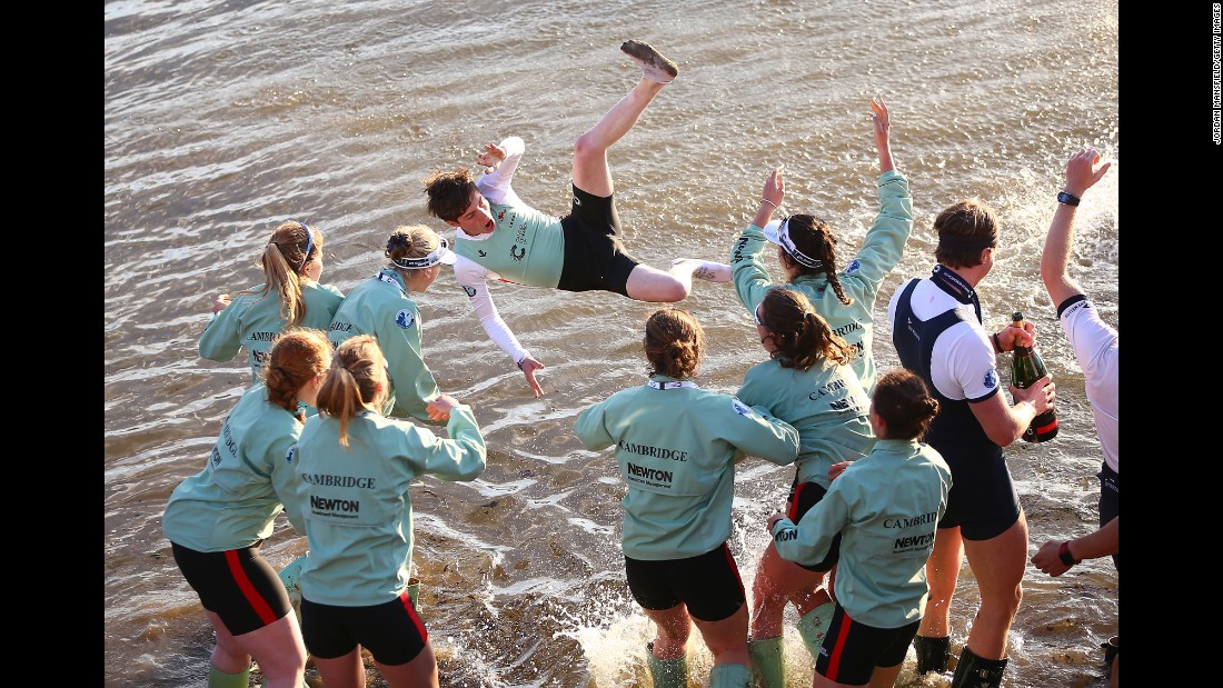 The women's crew from Cambridge celebrates its win in the annual University Boat Race by throwing Matthew Holland into London's River Thames on Sunday, April 2.