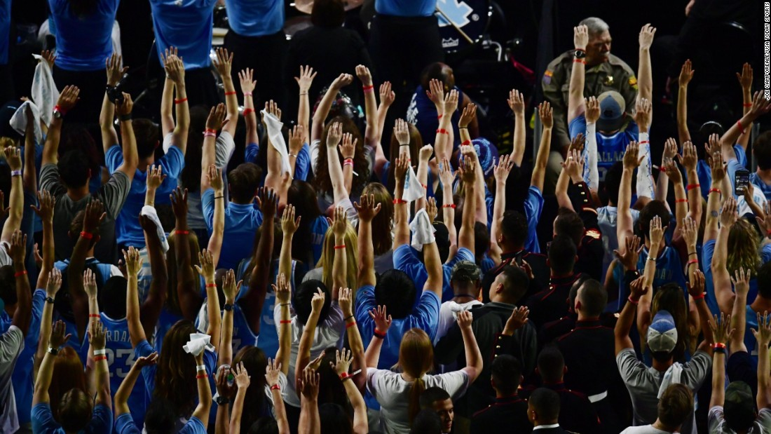 North Carolina fans hold up their hands.