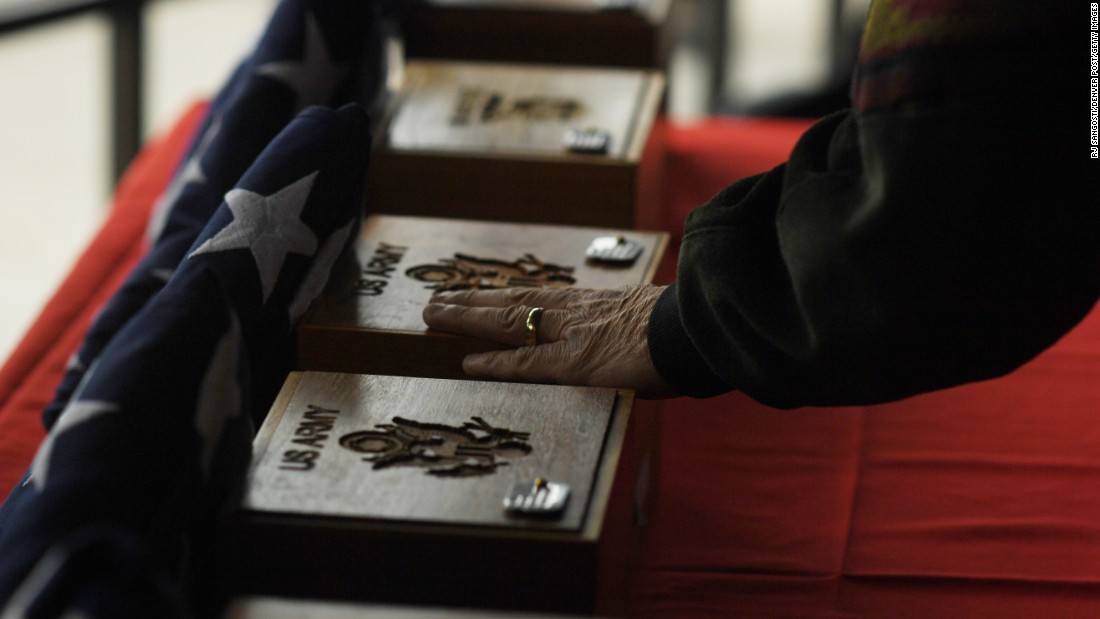 A man touches urns during a final interment ceremony in Denver on Friday, March 24. The unclaimed remains of 22 US veterans were honored at Fort Logan National Cemetery. The veterans served in wars such as World War II, the Korean War and the Vietnam War.