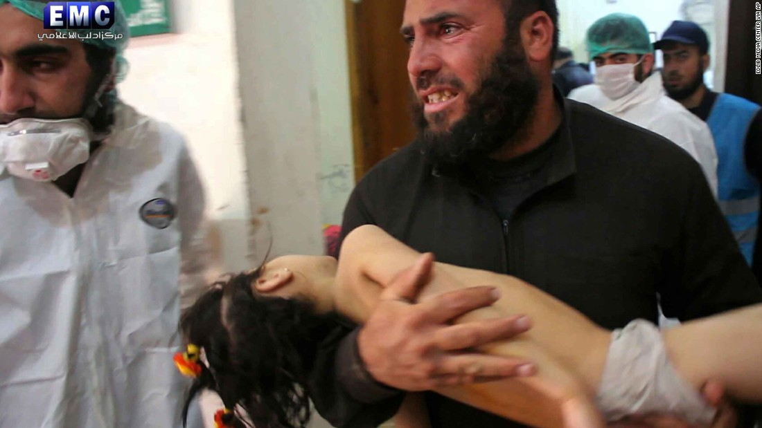 "A man carries a child at a makeshift hospital in Khan Sheikhoun. Activists have blamed the Syrian regime for the attack. In an apparent reference to the attack, two state-run Syrian media outlets reported that there was an explosion at a ""rebel poison gas factory"" in the countryside of Idlib province. The government has denied using chemical weapons in the past."