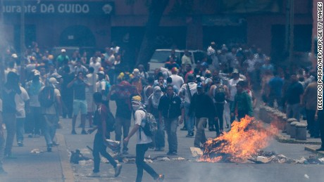 Opposition activists clash with riot police during a protest against President Nicolas Maduro's government in Caracas on April 4, 2017.  Activists clashed with police in Venezuela Tuesday as the opposition mobilized against moves to tighten President Nicolas Maduro's grip on power. Protesters hurled stones at riot police who fired tear gas as they blocked the demonstrators from advancing through central Caracas, where pro-government activists were also planning to march. / AFP PHOTO / FEDERICO PARRA        (Photo credit should read FEDERICO PARRA/AFP/Getty Images)
