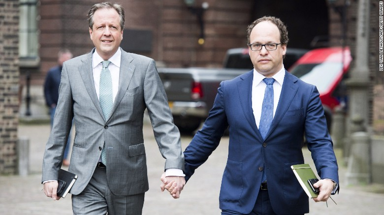 Men hold hands in solidarity with gay couple