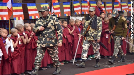 Indian security personnel walk past Buddhist monks as they wait for the Dalai Lama in Bomdila in India's northeastern state of Arunachal Pradesh on April 4, 2017.