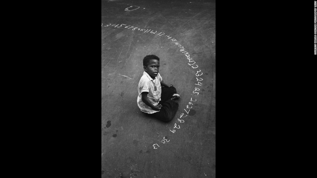 "A boy uses chalk to write numbers on a New York street in 1955. After Feinstein's death in 2015, <a href=""https://www.nytimes.com/2015/06/30/arts/harold-feinstein-dies-at-84-froze-new-york-moments-in-black-and-white.html"" target=""_blank"">The New York Times</a> called the photographer ""one of the most accomplished recorders of the American experience."""