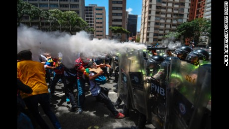 TOPSHOT - Venezuela's opposition activists clash with riot police agents during a protest against Nicolas Maduro's government in Caracas on April 4, 2017.