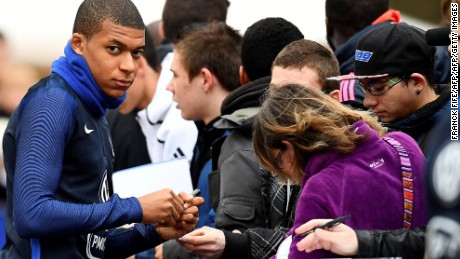French national football team forward Kylian Mbappe (L) signs an autograph before a training session.