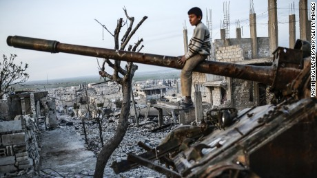A Syrian Kurdish boy sits on a destroyed tank in the Syrian town of Kobane, also known as Ain al-Arab, on March 27, 2015. Islamic State (IS) fighters were driven out of Kobane on January 26 by Kurdish and allied forces. AFP PHOTO/YASIN AKGUL        (Photo credit should read YASIN AKGUL/AFP/Getty Images)