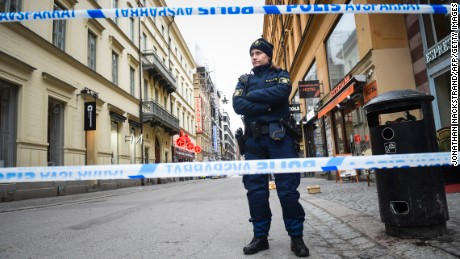 A police officer stands guard on April 8, 2017 at the site where a stolen truck was driven through a crowd and crashed into the Ahlens department store in central Stockholm the day before.
