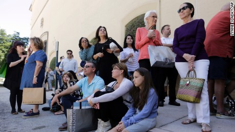 People sit outside the Shops at Merrick Park mall in Coral Gables after a shooting Saturday.