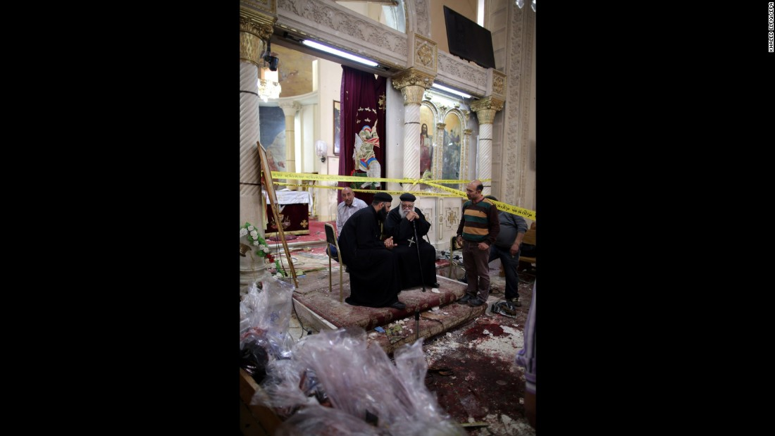 Priests sit next to security personnel investigating the scene of the bombing.