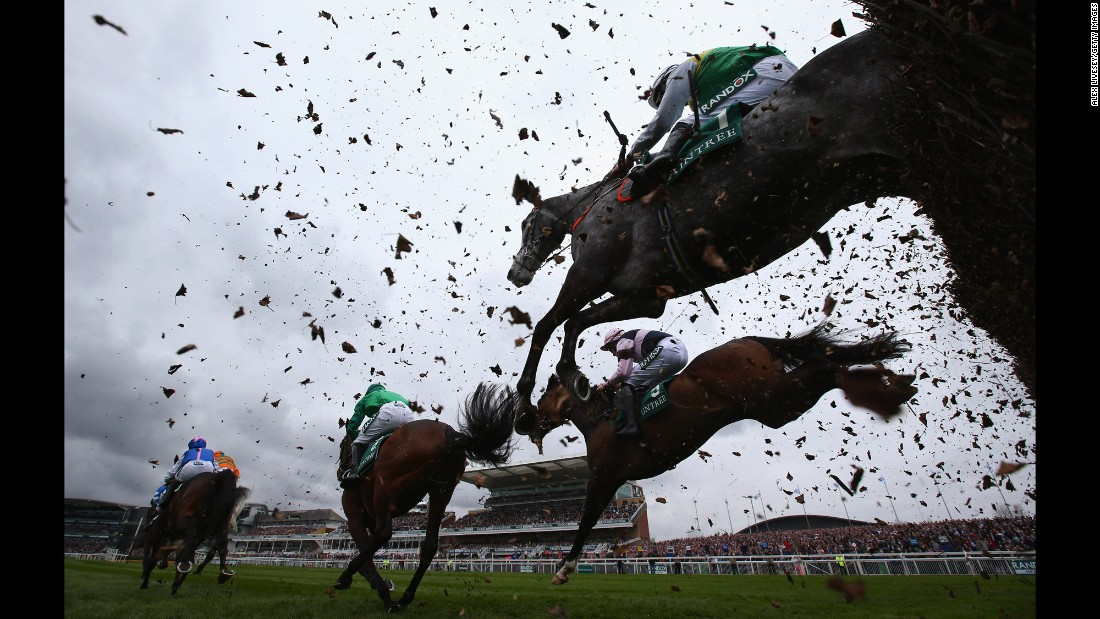 Horses clear a fence during a steeplechase in Liverpool, England, on Thursday, April 6.
