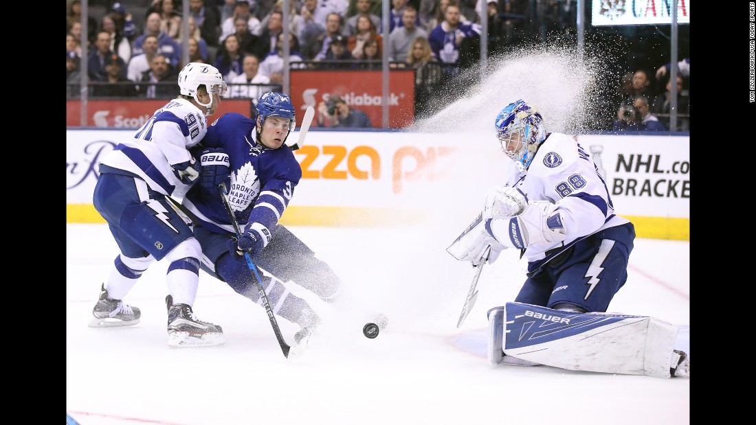 Toronto center Auston Matthews sprays Tampa Bay goalie Andrei Vasilevskiy as he tries to redirect a shot near the net on Thursday, April 6.