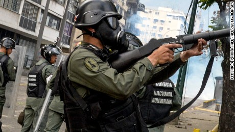 Venezuelan National Guard personnel in riot gear fire tear gas grenades at opposition activists in Caracas on April 10, 2017.  Venezuela's political crisis intensified last week when the Supreme Court issued rulings curbing the powers of the opposition-controlled legislature. The court reversed the rulings days later, but the opposition intensified its protests from that moment.  / AFP PHOTO / FEDERICO PARRA        (Photo credit should read FEDERICO PARRA/AFP/Getty Images)