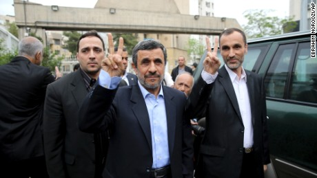 Former Iranian President Mahmoud Ahmadinejad, center, and his close ally Hamid Baghaei flash the victory sign as they arrive at the Interior Ministry to register their candidacy on Wednesday.
