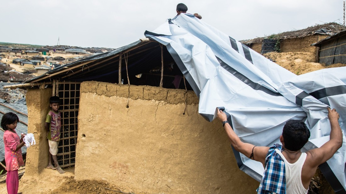 A family installing their new tarpaulin received from the Bangladesh Red Crescent Society (BDRCS) in the makeshift extension to Kutupalong camp.