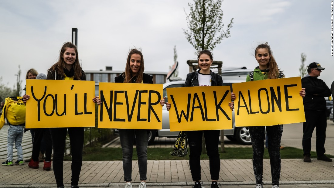 "Outside Dortmund's training ground Wednesday, four fans held a sign in support of their team which read ""You'll Never Walk Alone"" -- which is the title of the club's anthem."