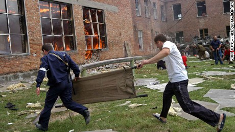 Two volunteers carry a stretcher as they approach the burning school during the rescue operation in Beslan, northern Ossetia, 03 September 2004.